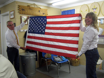 Lion Past President Kent Wakefield and Partner in Service Juli Wilson display a flag from the Olmsted Center.