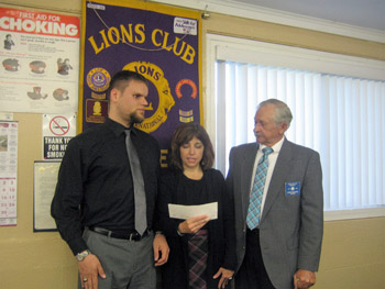 Ray Zylinski and Renee Diflavio from the Olmstead center accept a check from Barker Lions Club President Chris Czelusta.