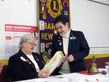 Lion District Governor receives a gift basket from Barker Lion President Fran Costello